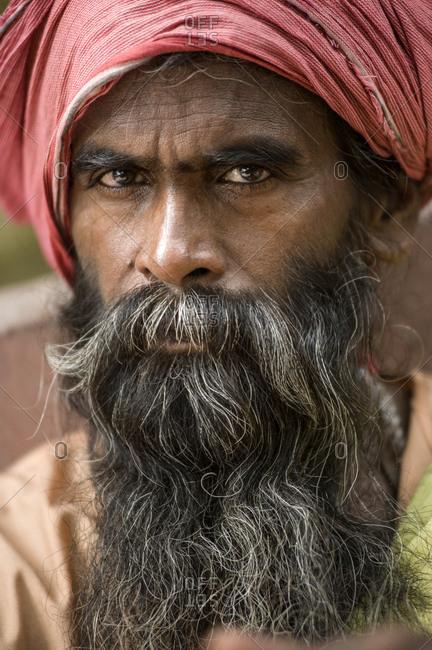 India, Uttarakhand, Rishikesh - July 16, 2011: Religious man with long beard and red turban