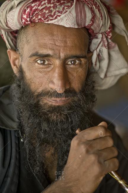 Pahalgam, Jammu and Kashmir, India - August 1, 2011: Native of Aru Valley with long beard and Keffiyeh, smoking a hookah