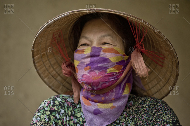 Old smiling woman wears Vietnamese hat and scarf