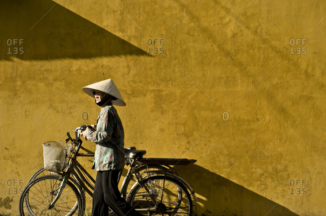Vietnam, Quang Nam Province, Hội An - February 23, 2011: Vietnamese woman with traditional Vietnamese hat carries her bicycle