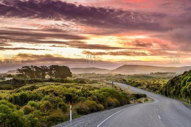 Country road with clouds at sunset, at the Catlins, South Island, New Zealand, Oceania