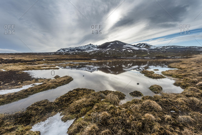 Hills reflected in snow melt, Reykjavik, Iceland, Europe