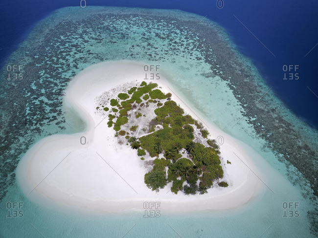 Heart-shaped, uninhabited palm island with sandy beach, offshore coral reef, Ari atoll, Indian Ocean, Maldives, Asia
