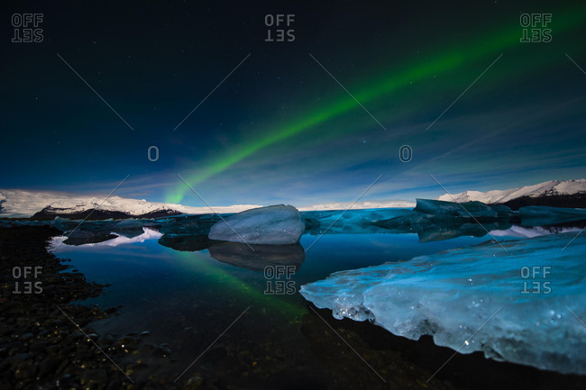 Chunks of ice in the water at the blue hour with polar lights, Jokulsarlon lake, Vik, Iceland, Europe