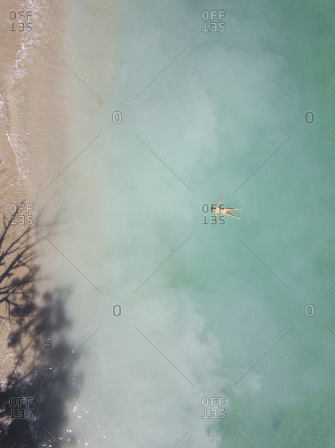 Young woman floating in water, Sumbawa, Indonesia