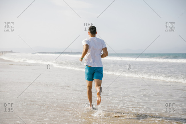 Young man jogging at the beach in the morning