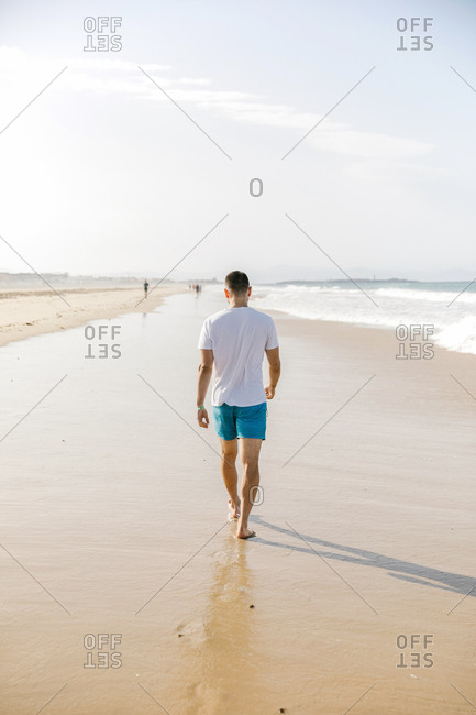 Young man walking at the beach by himself in the morning