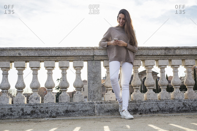Smiling woman using her phone while leaning on stone railing