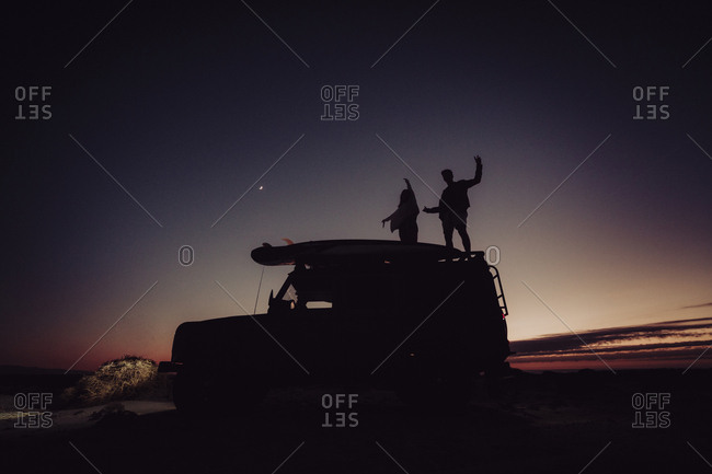 Couple standing on top of a 4x4 while camping during the blue hour