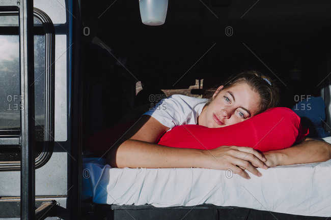 Girl waking up while camping in campervan