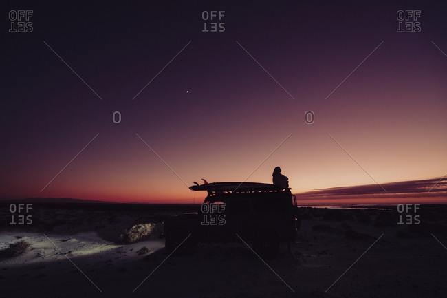 Girl on top of the 4x4 during the blue hour