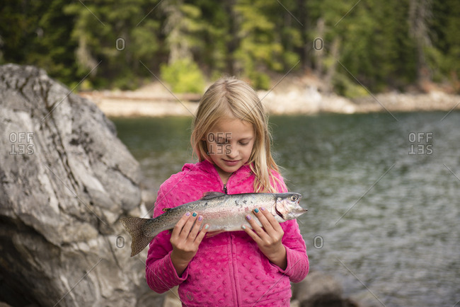 Portrait of 8-9 year old girl holding a fish at a lake