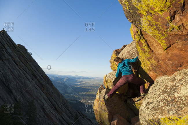 Woman climbs second flatiron without rope above boulder, colorado