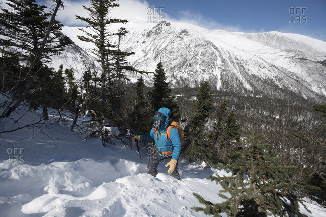 A woman hiking alone down a snowy slope with tuckerman ravine and the summit of mount washington in the background.
