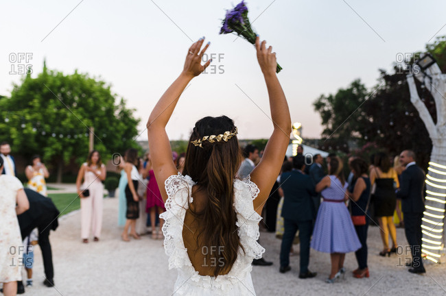 Back view of bride rising arms with bridal bouquet ready to throw