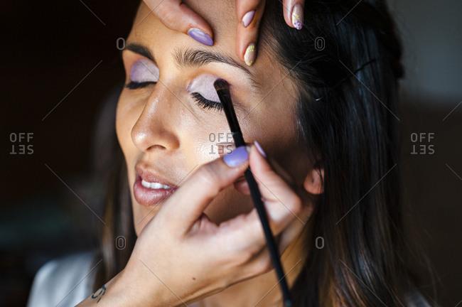 Make up artist applying eyeshadow on bride eye for wedding ceremony