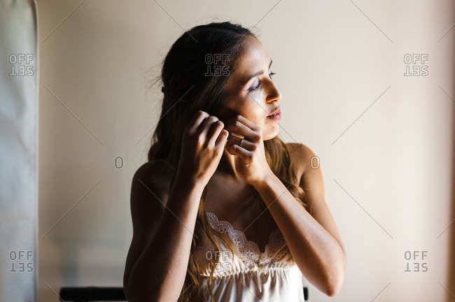 Portrait of a beautiful bride putting on earring