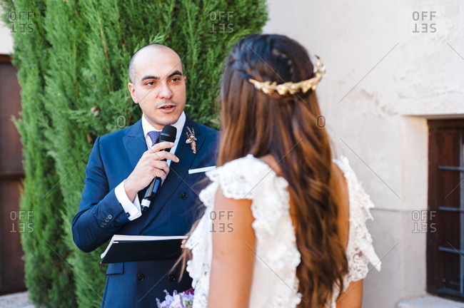 Bride and groom exchanging vows during ceremony with microphone