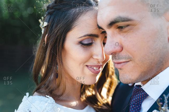 Close up of intimate newlyweds hugging each other with a lovely smile