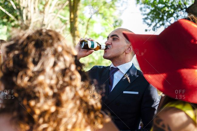Thirsty groom drinking beer surrounded by guests after wedding celeb