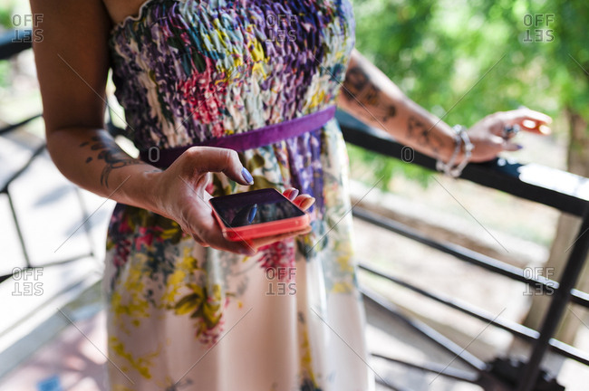 Wedding guest using smartphone dressed in colorful dress