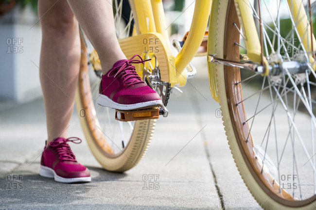 A woman's foot steps on the pedal of her yellow bike in preparation to ride