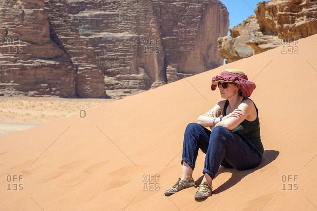 Tourist sits on sand dune in hot sun, wadi rum protected area, jordan
