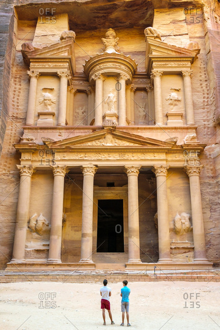 Two people stand in front of al-kazneh, the treasury, petra, jordan