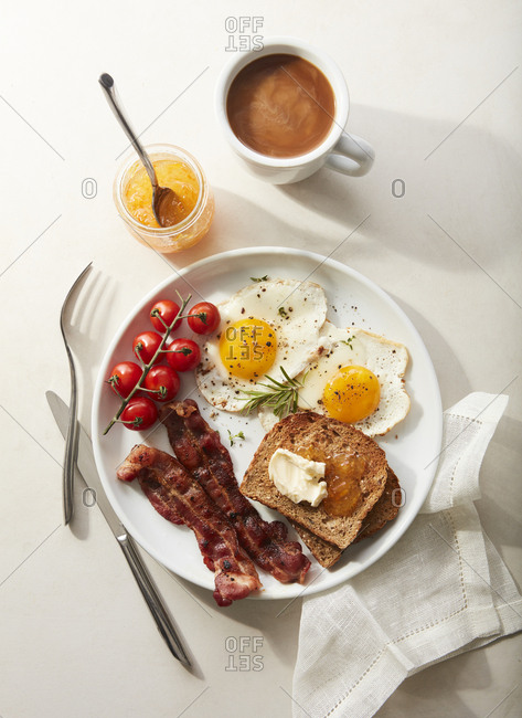 Two eggs sunny side up bacon, toast, jam, and coffee