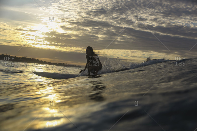 Young woman surfing at sunrise