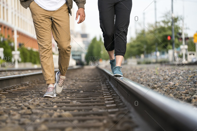 Young couple walking on train tracks in a city from the waist down