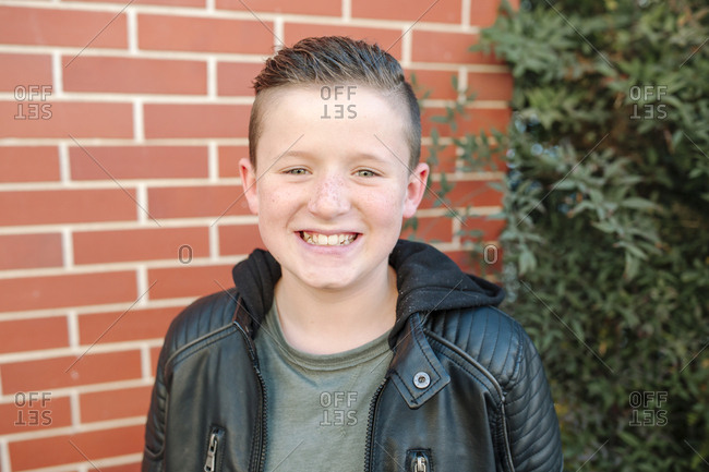 Happy preteen boy smiling in front of brick wall on sunny day