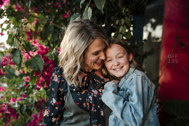 Smiling mother and daughter in front of red flowers on sunny day
