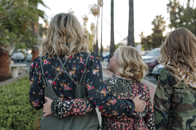Mom and daughters walking down street with palm trees