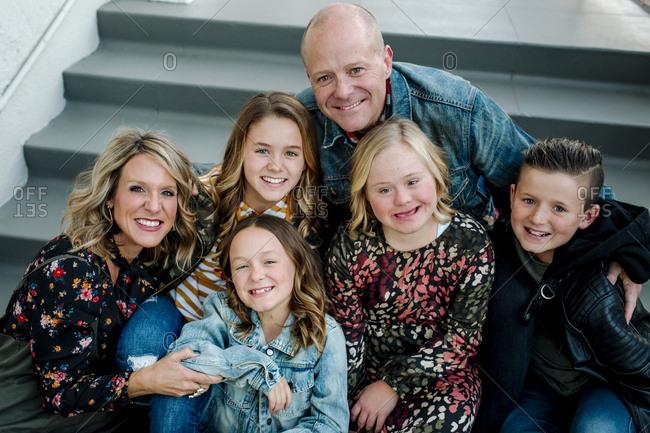 Diverse smiling family huddled on steps