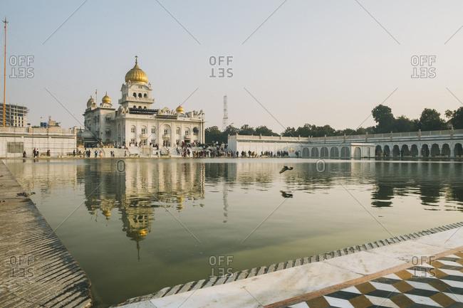 Sri bangla sahib gurudwara, new delhi, india - january 15, 2018: sri bangla sahib gurudwara reflection at sunset, new delhi, india