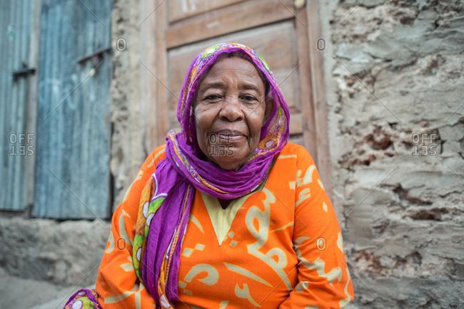 Kenya, lamu county, lamu - november 22, 2016: african muslim woman with purple headscarf and orange dress sitting