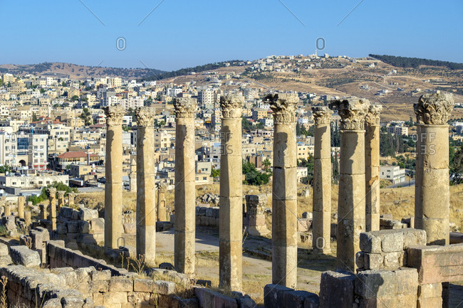 Jordan, jerash governorate, jerash - june 8, 2017: ruins of ancient roman city of gerasa with modern jerash in distance