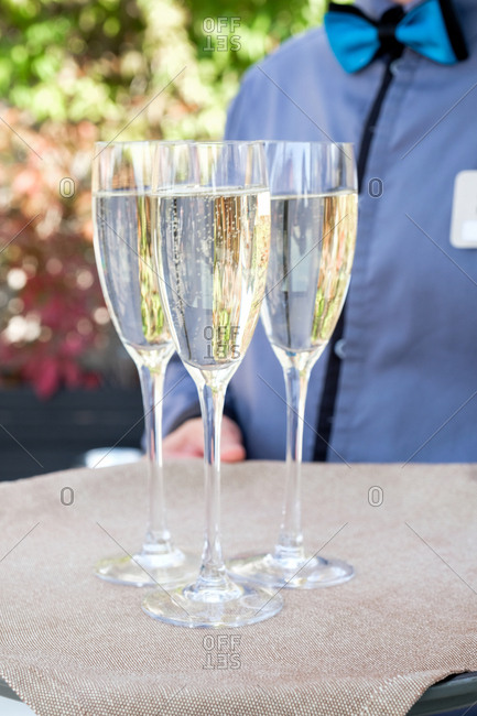 Server carrying two champagne glasses at an outside event