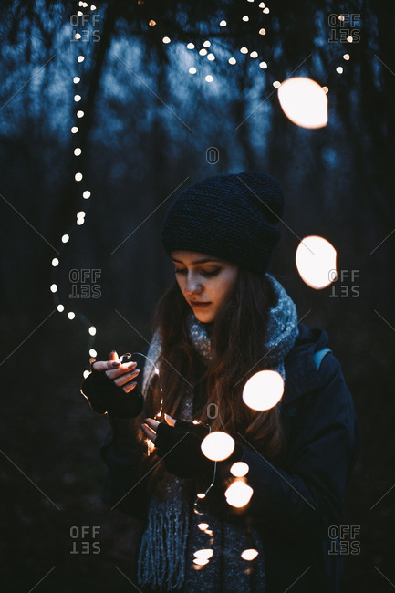Young hipster woman holding Christmas lights while standing in park