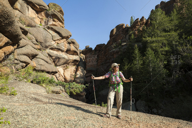 Senior woman hiker among rock formations in lost creek wilderness