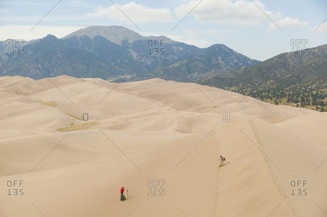 Senior couple explore sand dunes below mountains