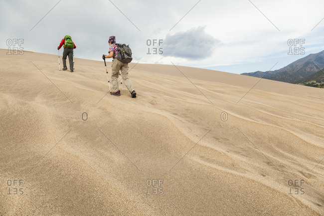 Senior couple ascend sand dune with ripples