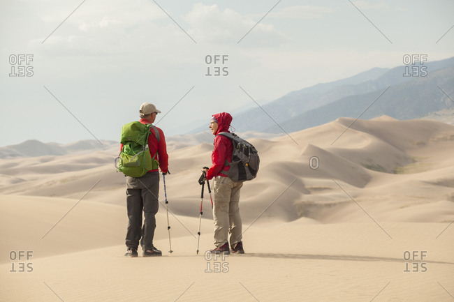 United States, Colorado, Great Sand Dunes National Park - August 9, 2018: Senior couple talk and enjoy view of sand dunes
