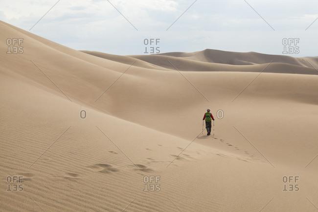 Man hikes across a sand dune