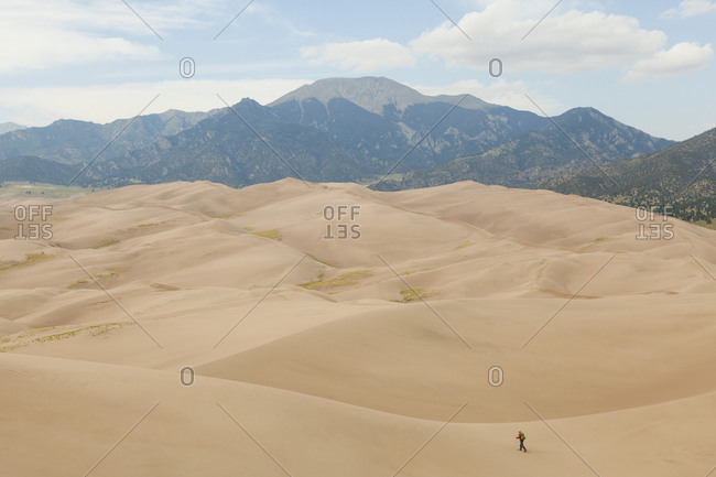 Man hikes across sand dunes with mountains in background
