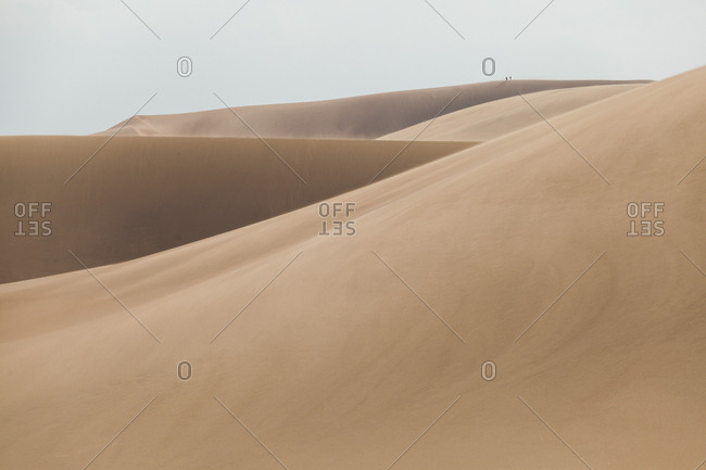 Hikers stand on summit of sand dune