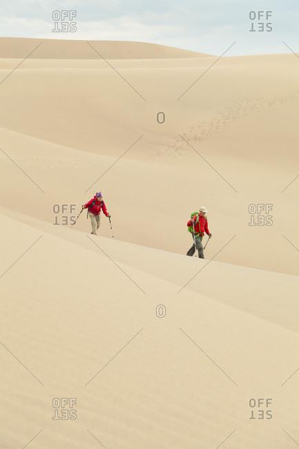 Senior couple hike across large sand dune