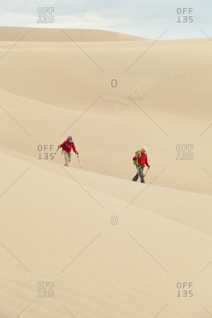 Senior couple hike across large sand dune