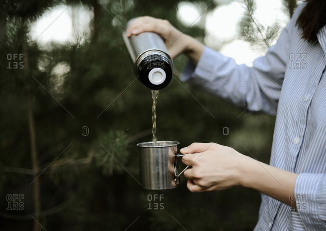 Close-up of woman pouring tea from insulated drink container int